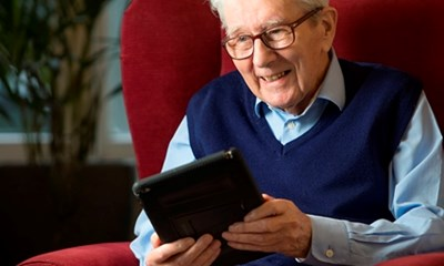 Elderly man holding a tablet