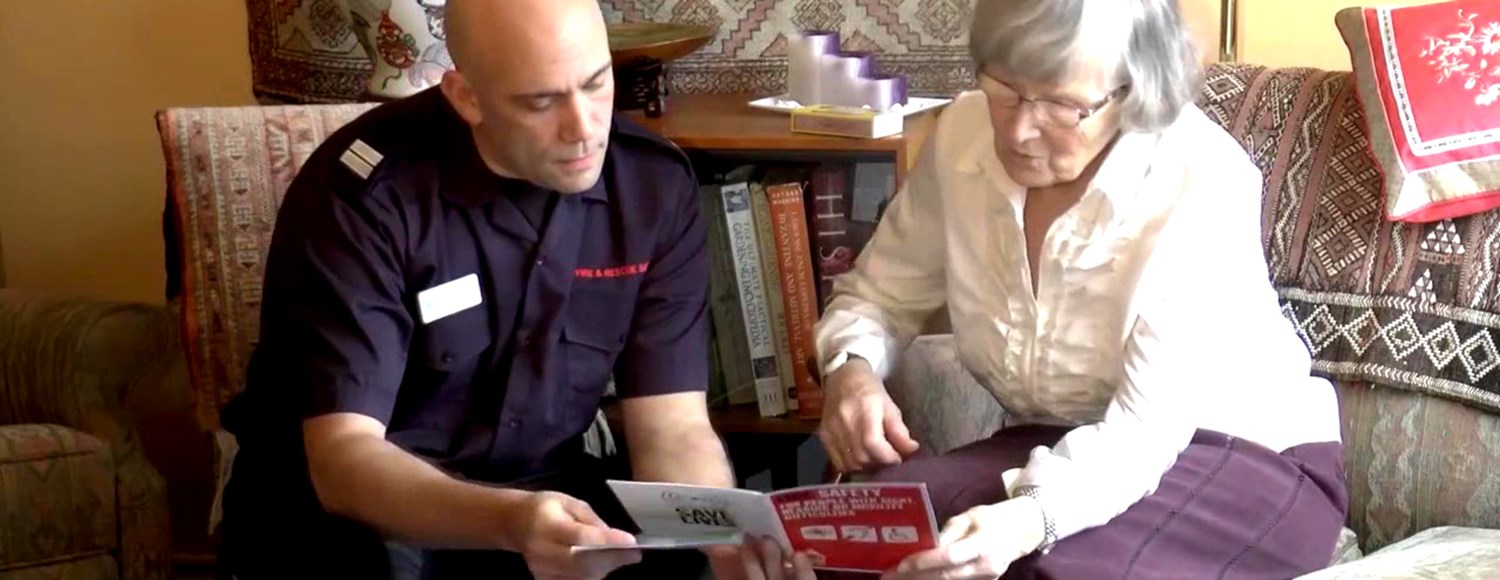 A firefighter speaks to an older relative in her home about fire safety as part of a Safe and Well Visit