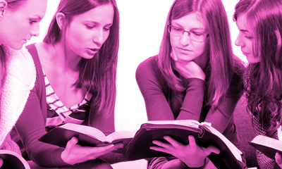 Two young women looking at a book