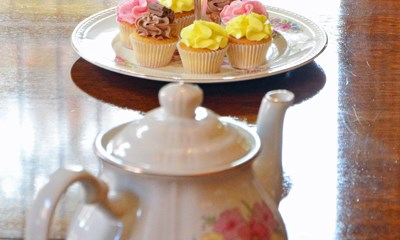 Delicious plate of cup cakes and a pot of tea
