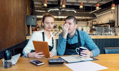 Restaurant owners looking worriedly at their accounts
