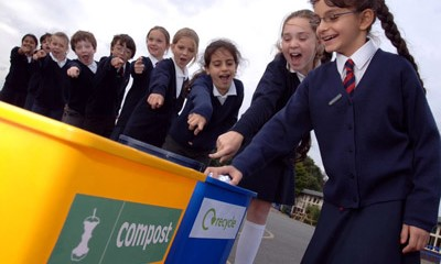 Group of school children pointing at 2 bins labelled 'compost' and 'recycle'.